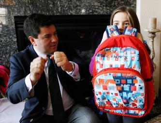 Колумбийский дизайнер Мигель Кабальеро демонстрирует шестилетней Лане как использовать один из пуленепробиваемых рюкзаков, которые он разработал для американских школьников. Стоимость рюкзака составляет $246. Аврора, штат Колорадо, США.